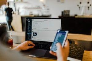 """Person sucht auf dem Handy und dem Laptop nach dem Begriff """"digitales marketing"""""""