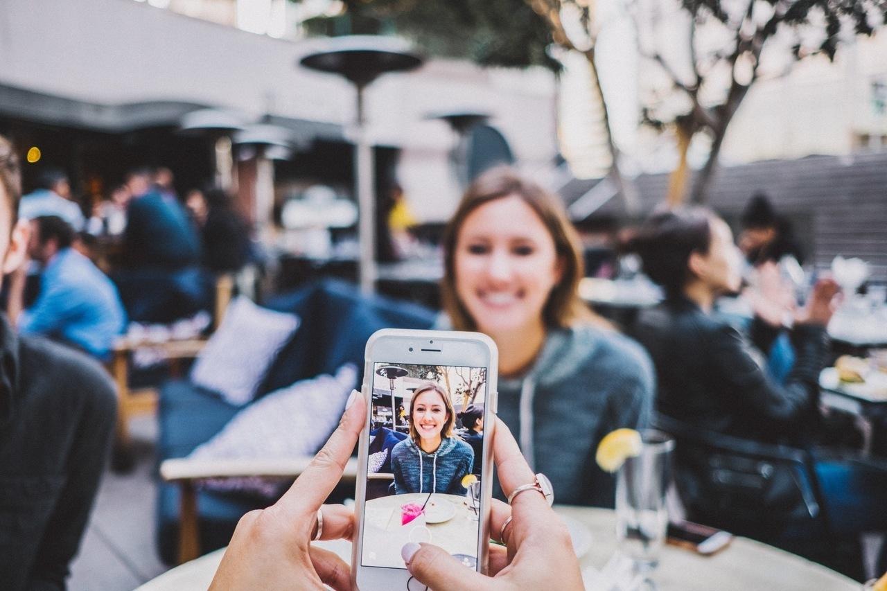 Frau wird mit dem Handy fotografiert, um das Bild auf den sozialen Medien zu teilen.